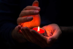hands protecting candle