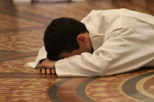 person with face to floor, sajda, sujood, prostration,